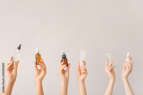 Female hands with different cosmetic products in bottles on grey background