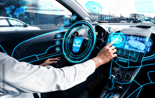 Canvas Print Self-driving autonomous car with relaxed young man sitting at driver seat is driving on busy highway road in the city