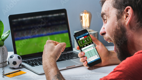 Foto Guy being happy winning a bet in online sport gambling application on his mobile