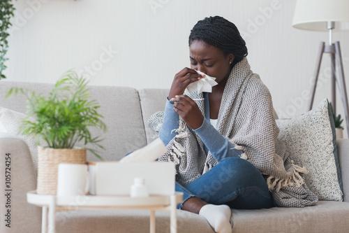 Fotografia Black girl having flu, blowing nose and checking body temperature