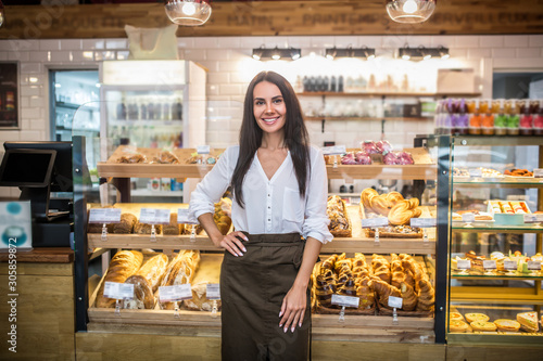 Cheerful young woman owning bakery feeling excited before starting work