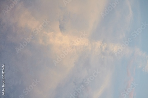 Low angle shot of the cloudy sky with the sun shining under the clouds