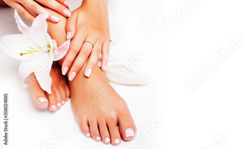 Fotografia manicure pedicure with flower lily closeup isolated on white perfect shape hands