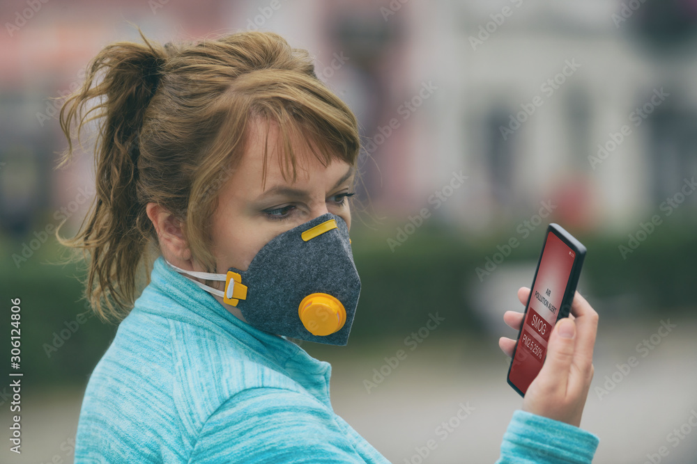 Woman wearing a real anti-smog face mask and checking current air pollution with smart phone app <span>plik: #306124806 | autor: Monika Wisniewska</span>