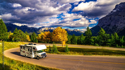 Fotografiet Recreational Vehicle Driving on Autumn Highway In Beautiful Mountains Wilderness