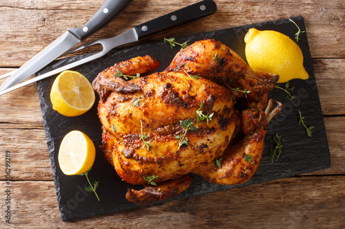 Tableau sur Toile Homemade chicken rotisserie with thyme, lemon closeup on a slate board