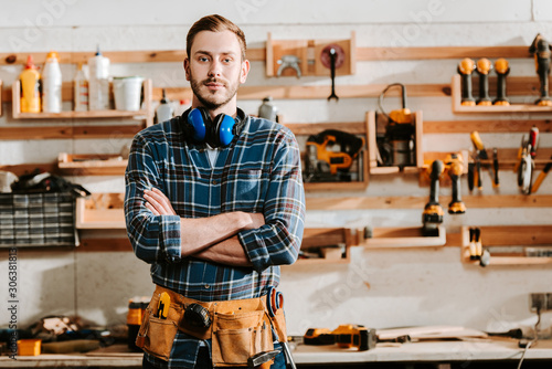 Fotomural handsome carpenter in apron standing with crossed arms in workshop
