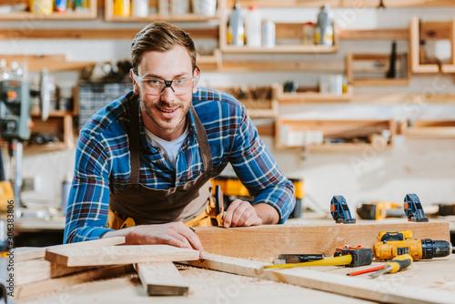 selective focus of happy carpenter in goggles touching wooden dowel Fototapeta