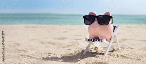 Stampa su Tela Pink Piggybank On Deck Chair Over The Sandy Beach