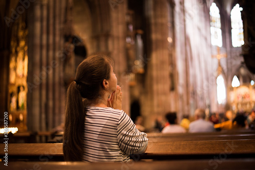 Young girl praying in church standing on her knees