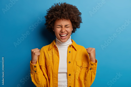 Valokuva Happy dark skinned woman enjoys moment of success, celebrates victory or great r