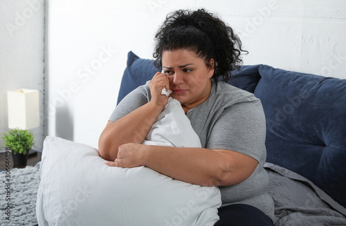 Vászonkép Depressed overweight woman crying while hugging pillow on bed