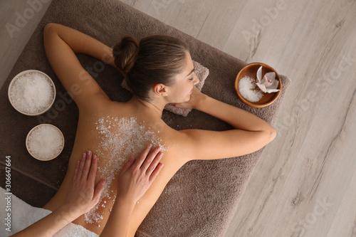 Fotografiet Young woman having body scrubbing procedure with sea salt in spa salon, top view