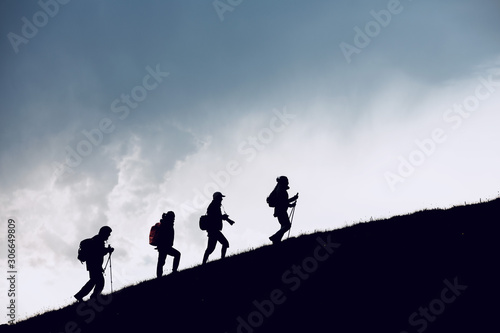 Valokuva Four hikers silhouettes goes uphill