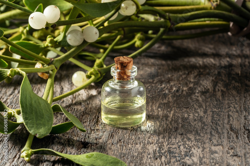 Fotografia A bottle of essential oil with fresh mistletoe