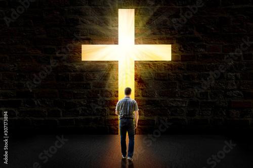 Foto a man walking towards a glowing cross