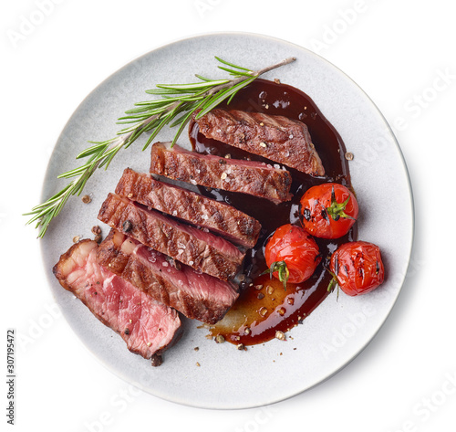 Fototapeta Grilled sliced Beef Steak with sauce, tomatoes and rosemary on a white plate Iso