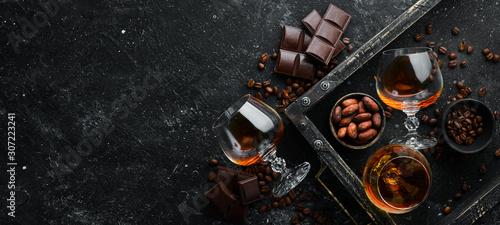 Fotografia Brandy and chocolate on a black stone table