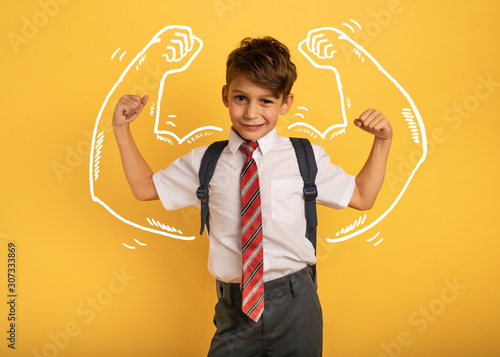 Stampa su Tela Young boy student acts like a muscled man. Yellow background