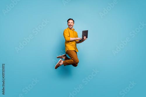 Obraz na plátně Full size photo of funky man feel rejoice emotions jump use laptop search social