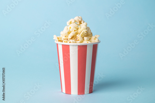 Popcorn in disposable box isolated on blue.