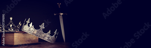 Fotografia low key image of beautiful queen/king crown over antique book next to sword