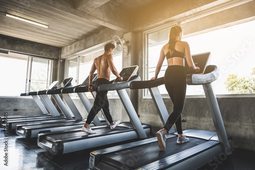 Man and woman Exercising by running on the treadmill To maintain good health alw Fototapeta