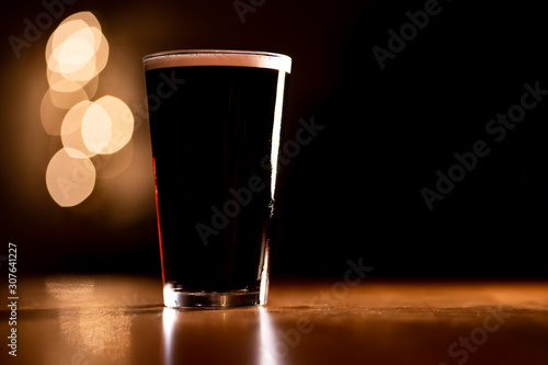 Wallpaper Mural Pint of Dark Stout Beer on a Wooden Table with Copy Space