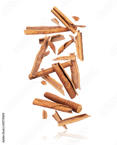 Photographie Cinnamon sticks are falling down in chaotic order on a pile on a white backgroun