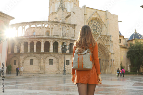Tourism in Valencia. Back view of beautiful girl visiting Valencia Cathedral on sunny day. Holidays in Spain.
