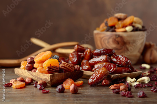 Fototapeta Various dried fruits and nuts in wooden dish.
