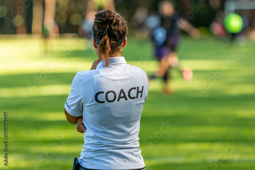 Foto Back view of a female sport coach watching her team compete at an outdoor footba