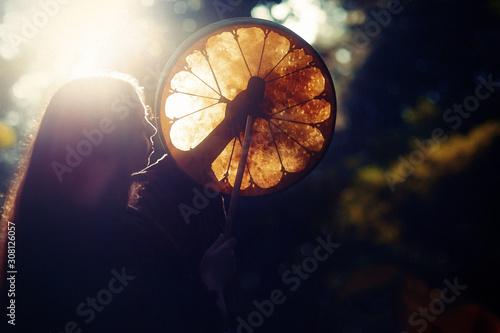 Stampa su Tela beautiful shamanic girl playing on shaman frame drum in the nature