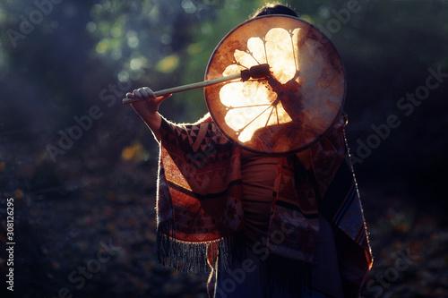 Fotografia beautiful shamanic girl playing on shaman frame drum in the nature