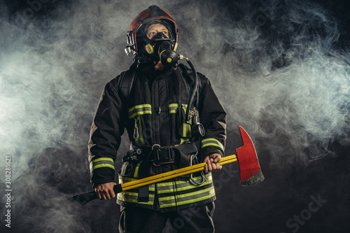 Fotografia young caucasian fireman holding hammer, risking his life to save people from fir