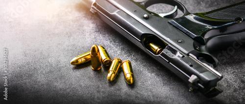 Fotografia Hand gun with ammunition on dark stone background