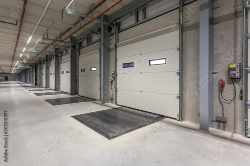 Fotografie, Tablou Row of loading docks in a warehouse with turned-on lights on the ceiling