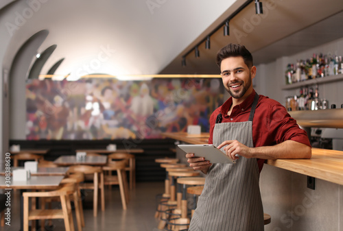 Young male business owner with tablet near counter in his cafe. Space for text