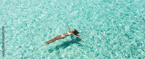 Photo Woman in white bikini lying on transparent turquoise water surface on beach