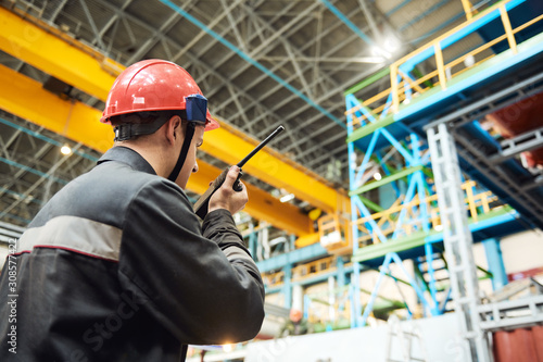 Fotografering industrial worker on factory with walkie talkie transmitter