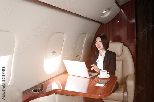 Valokuvatapetti Businesswoman with laptop on board the modern private airplane