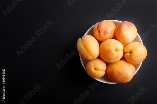 Fotografía Fresh orange apricots in white bowl on black background