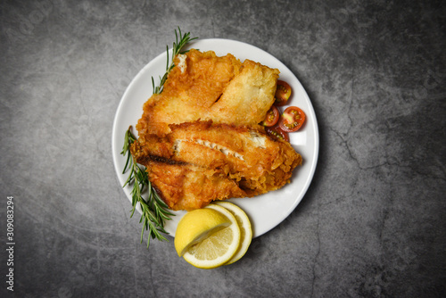 Fototapeta fried fish fillet sliced for steak or salad cooking food with herbs spices rosem