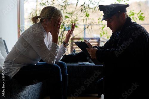 Photo Policeman interviews victims after burglary and theft