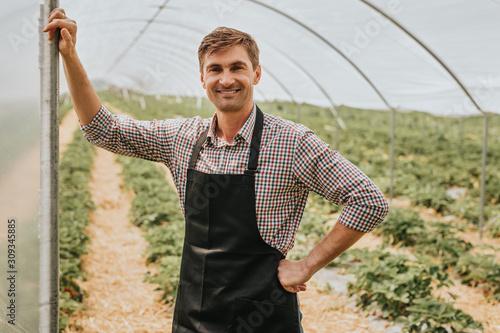 Obraz na płótnie Smiling plant breeder in black apron at entrance to greenhouse