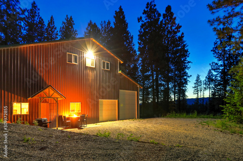 Fototapeta Large metal barn at night with fire at round table and outdoor furniture