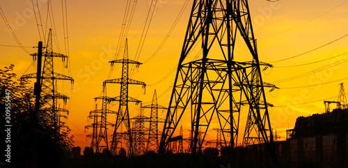 Canvas Print Electricity pylons bearing the power supply across a rural landscape during sunset