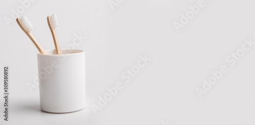 Holder with eco bamboo toothbrushes on white background Fototapeta