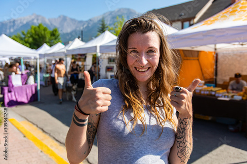 Fotografia A healthy caucasian girl gives the thumbs up at local street fair for artisans a