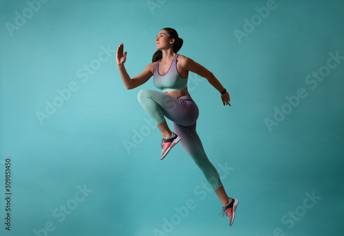 Fotografia Athletic young woman running on turquoise background, side view